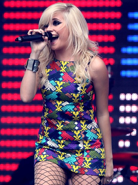 Pixie Lott performing in red and green dress