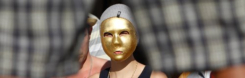 Justin Bieber wears a gold mask