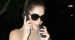 Cheryl Cole holding 3 mobile phones
