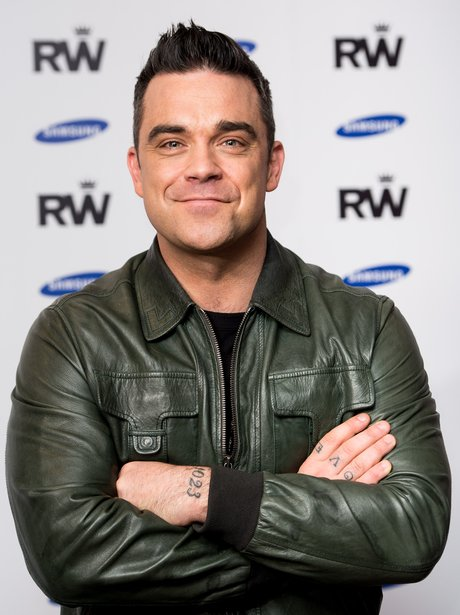 Robbie Williams in a leather jacket with his arms crossed